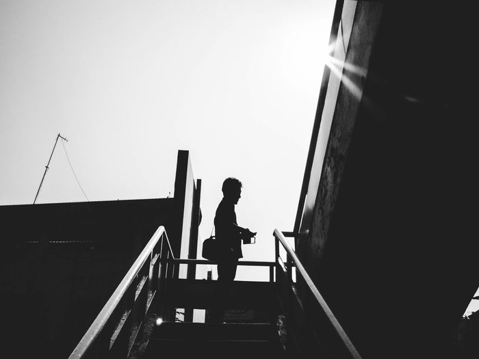 Low angle view of woman standing on railing