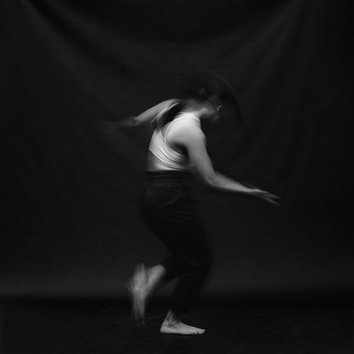 Side view of woman dancing against black background