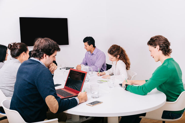 Businessman and female entrepreneurs working by conference table in office