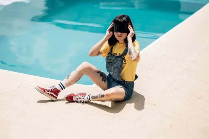 Paint The Town Yellow Water Swimming Pool High Angle View One Person Leisure Activity Day Sitting Outdoors Real People Full Length Vacations Lifestyles Young Women Young Adult Shadow Nature People