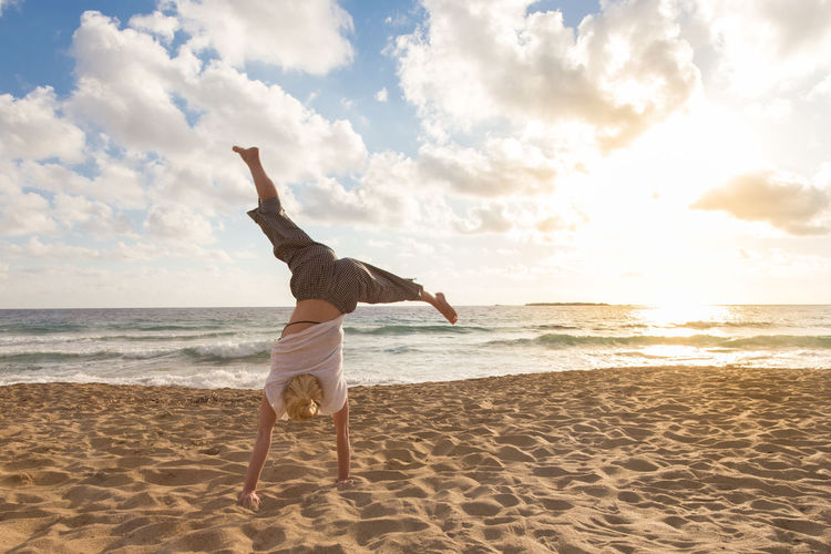 Full length of woman with performing handstand on beach against sky
