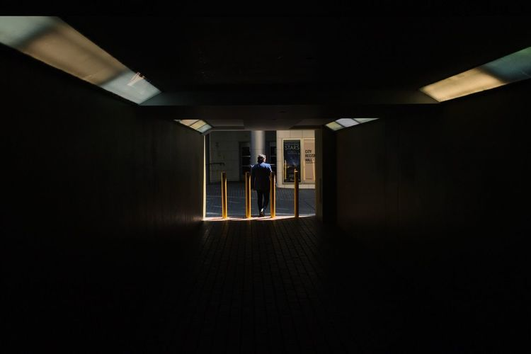 People in illuminated corridor