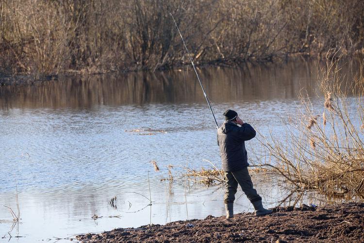 Side view of man fishing in lake
