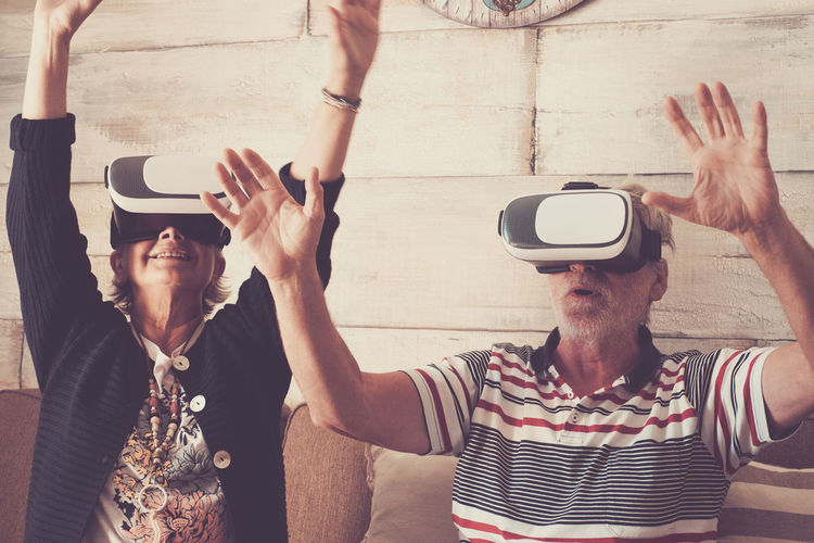 Senior couple wearing virtual reality headset at home