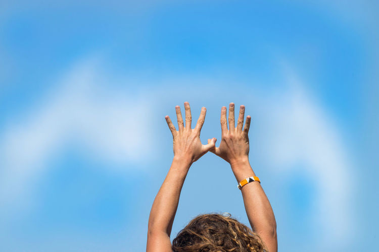 Woman with arms raised against blue sky