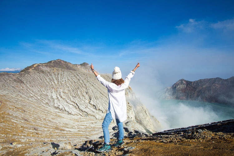 INDONESIA Travel Arms Raised Beauty In Nature Blue Sky Casual Clothing Day Geology Human Arm Kawah Ijen Land Leisure Activity Lifestyles Limb Mountain Nature Non-urban Scene One Person Outdoors Physical Geography Real People Scenics - Nature Sky Smoke - Physical Structure Standing Sunlight Tourism