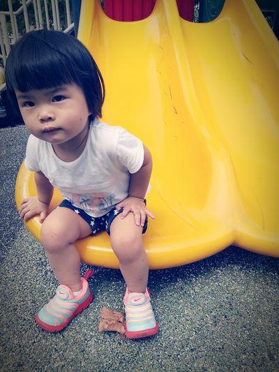 Portrait of cute girl sitting on yellow slide