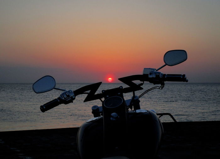 Motorcycle by sea against sky during sunset