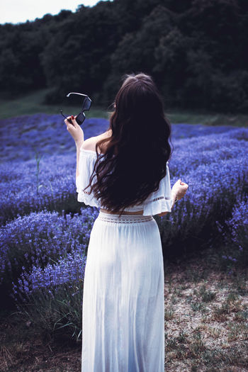 Rear View Of Woman Standing At Lavender Field