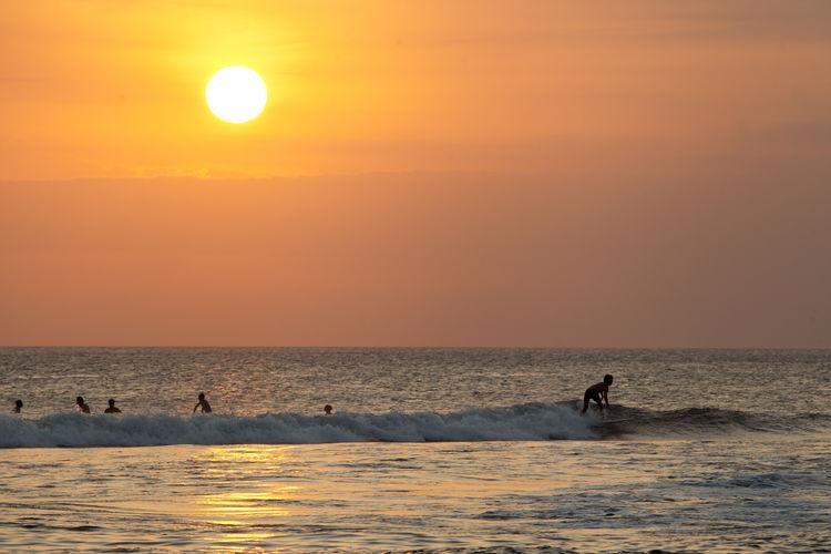 Silhouette man surfing in sea against orange sky