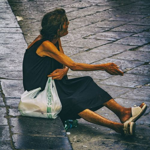 Side view of woman sitting on footpath