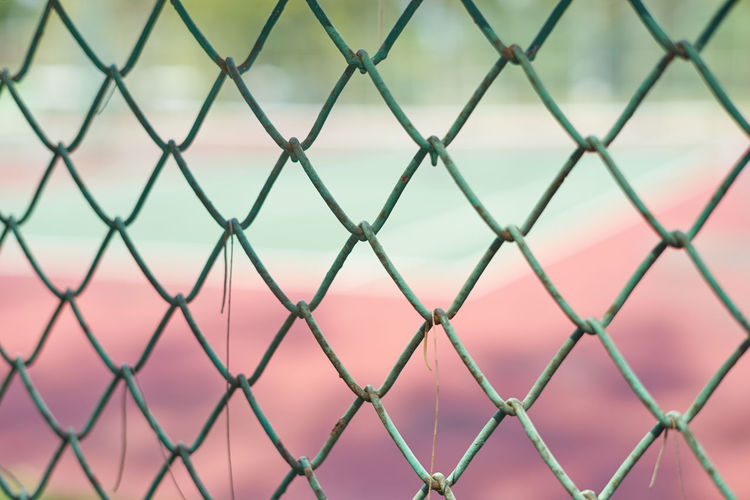 The net of tennis field Backgrounds Blur Chainlink Fence Close-up Court Crisscross Day Fence Fences Fench Field Full Frame Green Metal Net No People Outdoors Pattern Protection Red Safety Security Textured