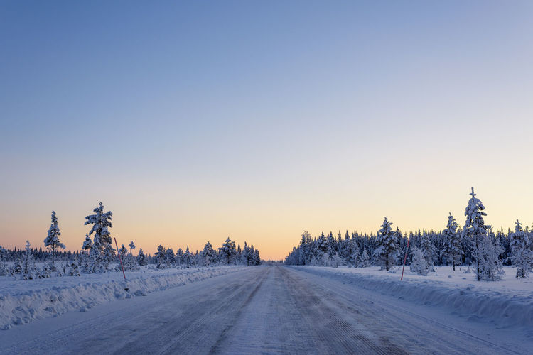 Snow covered landscape against clear sky