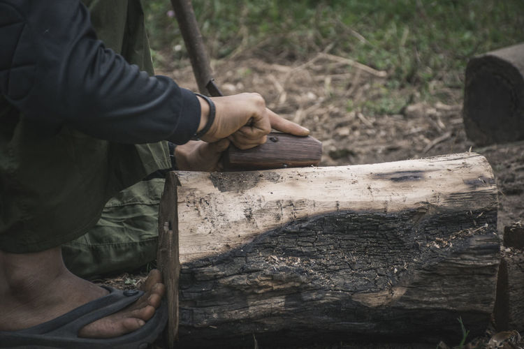 Low section of man carving wood