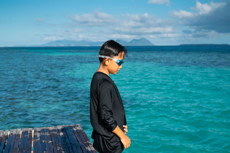 Side view of boy standing on pier over sea against sky