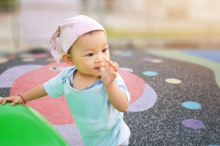 Baby girl sucking thumb finger at the playground. She's practice to standing and walking. Asian  Infant Finger Sucking Thumb Sucking Playground Child Childhood Baby Young Real People Babyhood Innocence Day One Person Toddler  Front View Focus On Foreground Clothing Cute Hat Casual Clothing Lifestyles Outdoors Warm Clothing Portrait