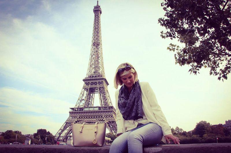 Mid adult woman sitting against eiffel tower