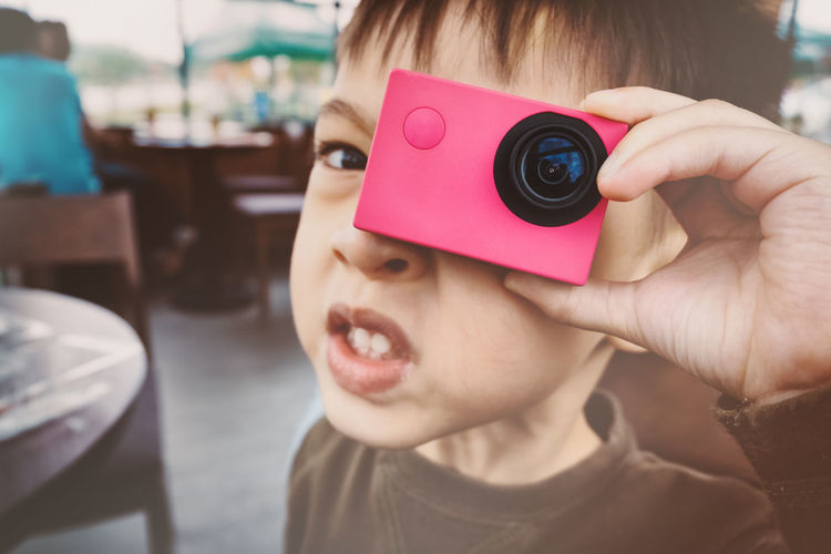 Close-up portrait of boy photographing with wearable camera