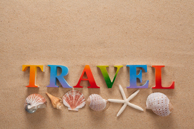 Directly above shot of travel text with seashells on sand at beach