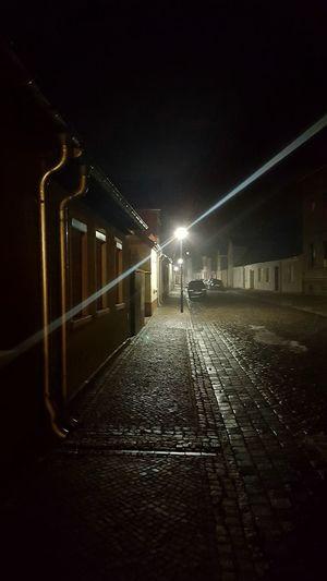 Illuminated walkway against sky at night