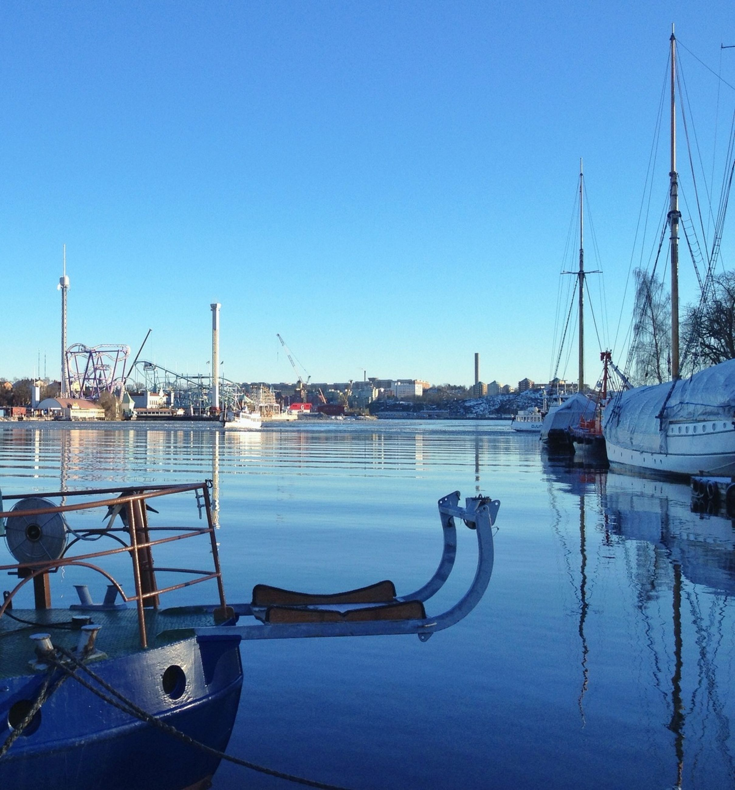 nautical vessel, transportation, mode of transport, moored, clear sky, boat, water, harbor, copy space, blue, mast, commercial dock, waterfront, sailboat, sea, river, reflection, travel, marina, outdoors