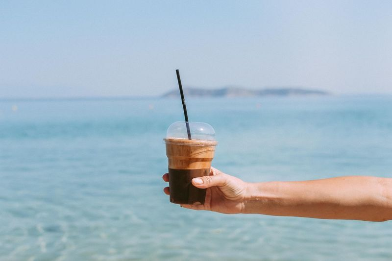 Cropped hand holding coffee against sea