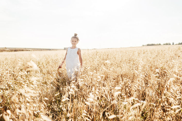 Portrait of cute girl standing in farm against sky
