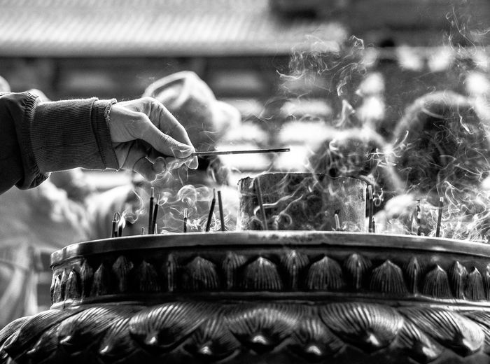 Cropped Hand Holding Incense At Temple