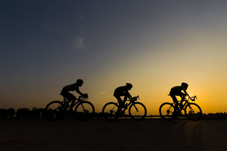 three cyclist in sunset Activity Bicycle Group Of People Land Land Vehicle Leisure Activity Lifestyles Men Mode Of Transportation Nature Orange Color Outdoors People Real People Ride Riding Silhouette Sky Sport Sun Sunset Transportation