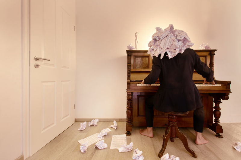 Rear view of man playing piano amidst scattered crumpled papers in room
