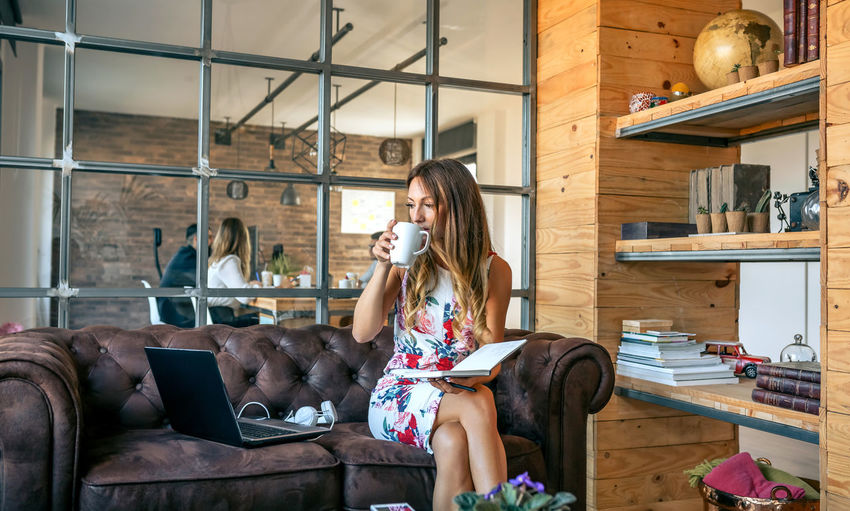 Woman using mobile phone while sitting in laptop