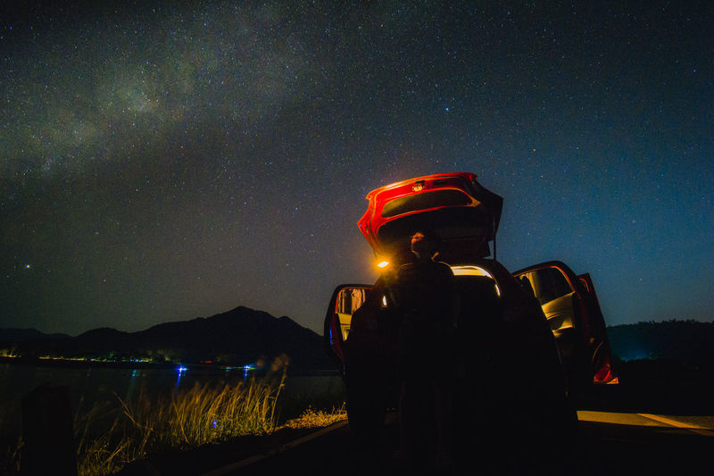 Rear view of man standing on illuminated car on road against sky at night