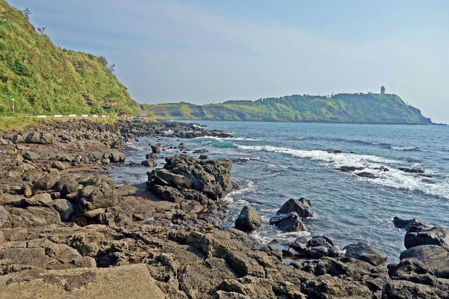 a Suwolbong volcanic cone scenery over a sea and basaltic rocks from a Eongal coastal walking trail,jeju island,korea,asia Suwolbong ASIA Basalt Beach Beautiful Cone Eongal Island Jeju Korea Mountain Nature Rocks Sea Shore Sky Trail Tranquility Travel Trip View Volcanic  Walking Water Wave