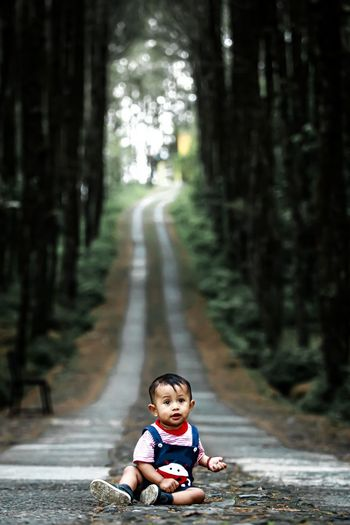 Full length of boy on footpath in forest