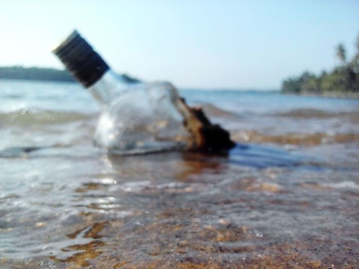 Close-up of bottle on beach against sky
