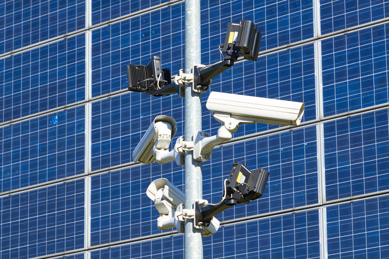 Low Angle View Of Security Cameras Against Solar Panels