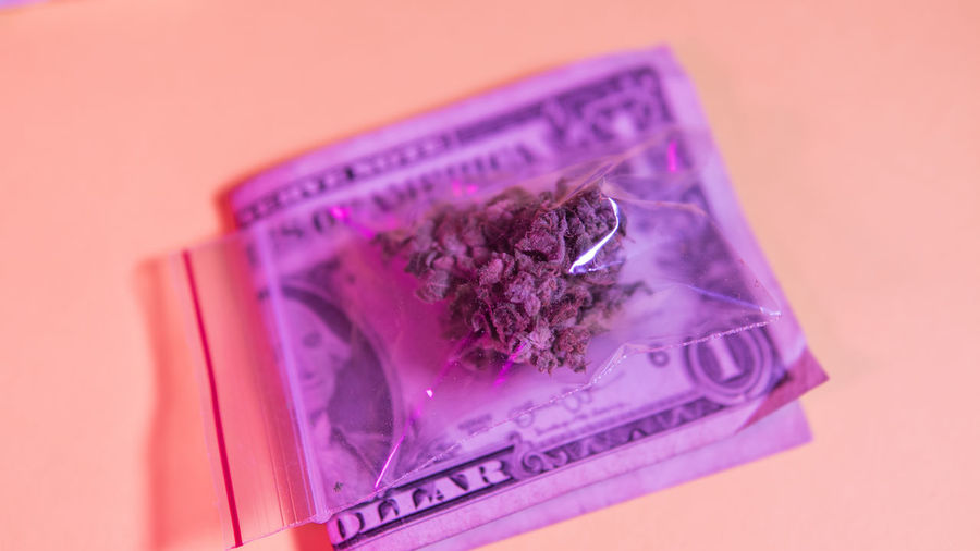 High Angle View Of Marijuana On Paper Currency Over Table