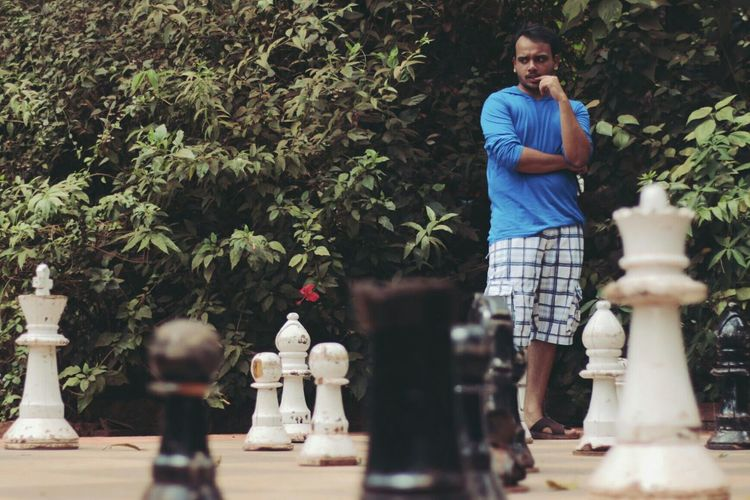 Young man contemplating on chess board
