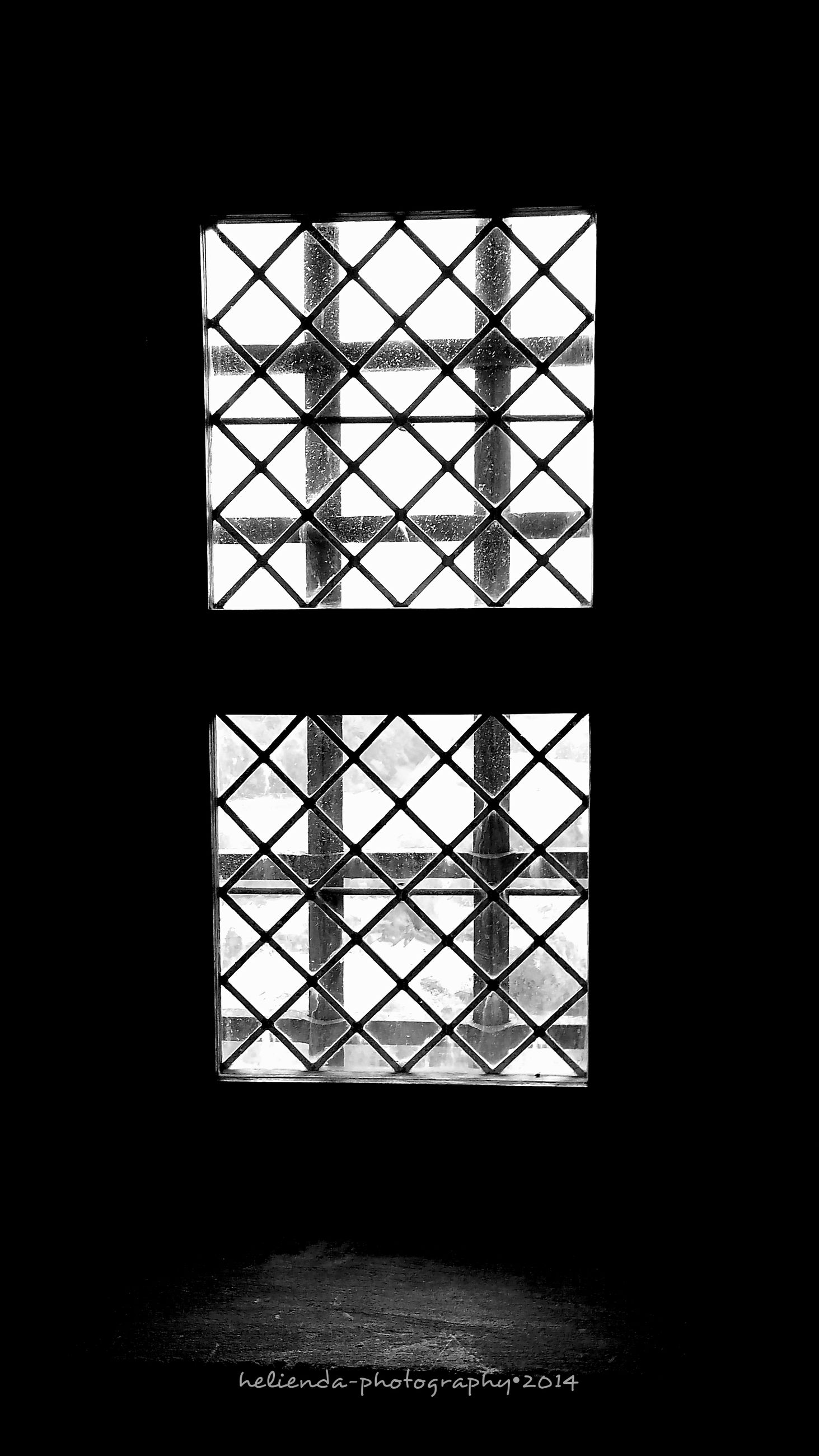 indoors, low angle view, silhouette, window, built structure, architecture, dark, geometric shape, glass - material, skylight, metal, transparent, no people, clear sky, grid, pattern, ceiling, day, sky, copy space