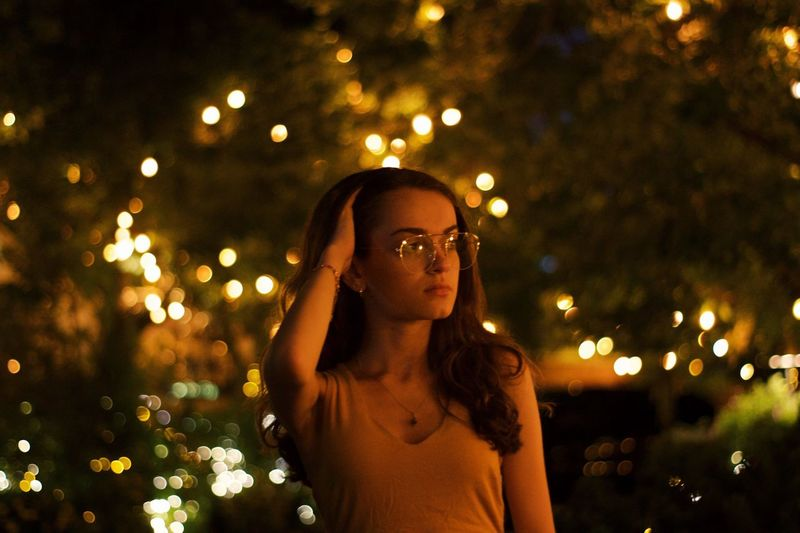 Portrait of young woman standing against illuminated trees at night
