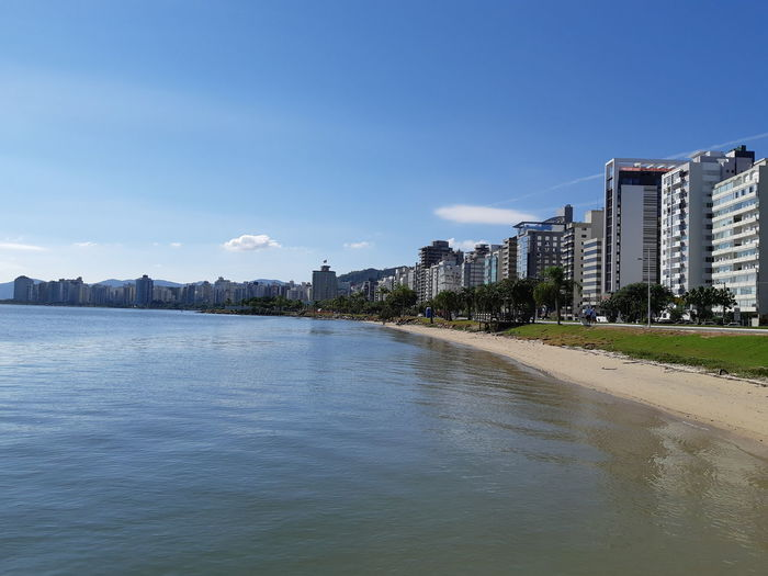 Panoramic View Of Sea And Buildings Against Blue Sky