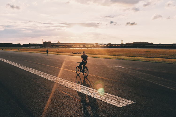 Man riding bicycle on road against sky during sunset