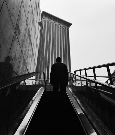 Rear View Of Man Standing On Escalator By Building