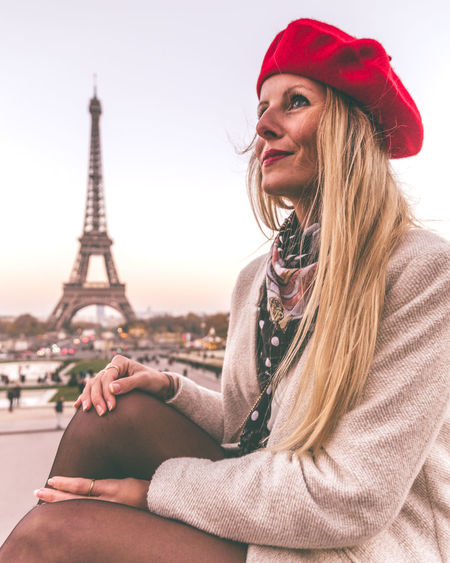 Beautiful young woman wearing hat against eiffel tower in city