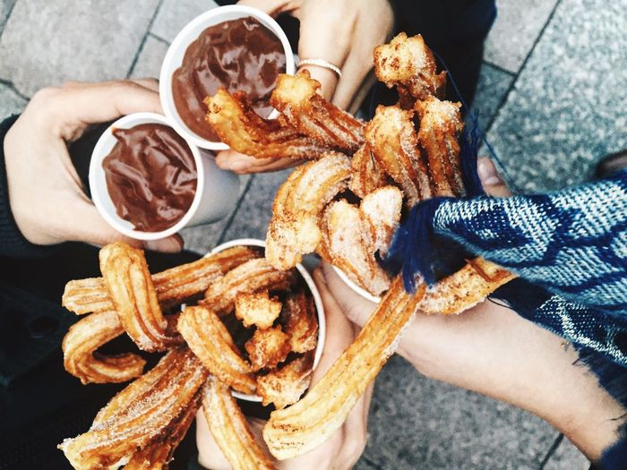 Cropped image of friends holding fresh churros and hot chocolate