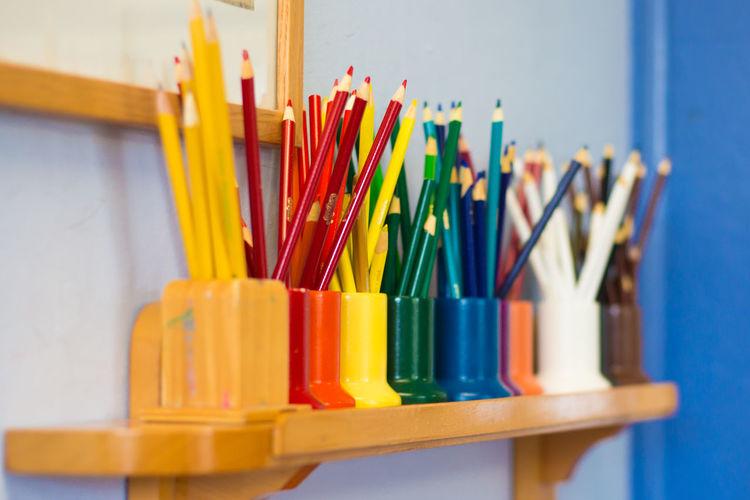 Colorful pencils in desk organizers on shelf