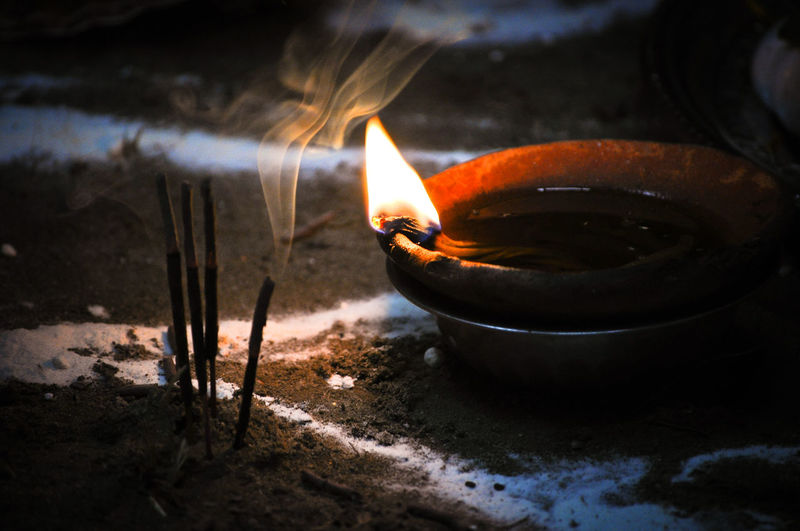 Close-up of lit diya by incense on ground