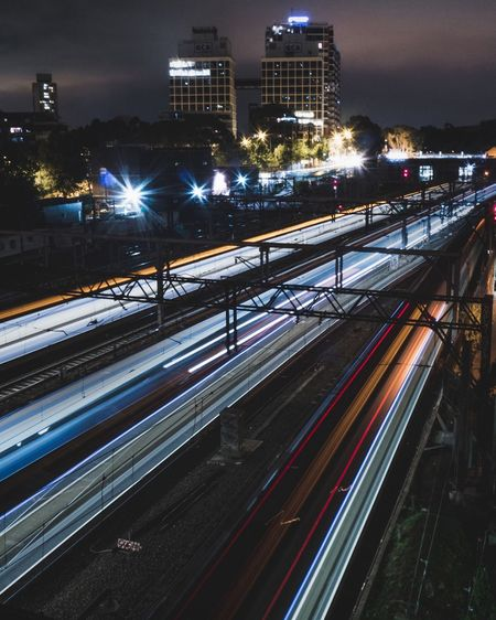 Blurred image of trains moving on tracks at night