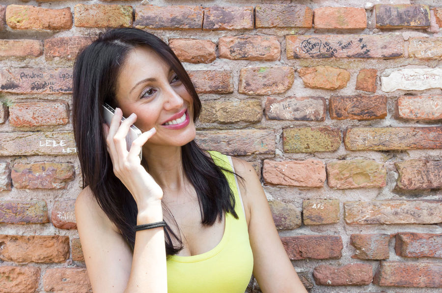 Woman talking on the phone and smiling outdoors. Behind her is a red stone wall. Adult Attractive Background Beautiful Brunette Call Caucasian Cell Cellphone Cute Female Girl Happy Isolated Lifestyle Mobile Model People Person Phone Portrait Pretty Red Smartphone Smile