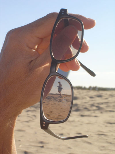 Woman seen from eyeglasses held by man at beach